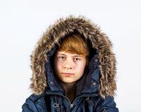 Muchacho adolescente que desgasta un anorak con la piel falsa alrededor del capo motor Imágenes de archivo libres de regalías