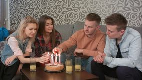 Muchacho adolescente que enciende una vela del cumpleaños en la torta con los amigos en casa Foto de archivo