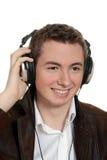 Muchacho adolescente que escucha la música con los auriculares Imagenes de archivo