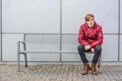 Muchacho adolescente que espera y que se sienta en el banco del metal al aire libre en ciudad Foto de archivo libre de regalías
