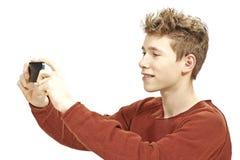 Muchacho adolescente que fotografía con un smartphone Imágenes de archivo libres de regalías