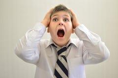 Muchacho adolescente que grita llevando a cabo sus manos detrás de la cabeza Foto de archivo libre de regalías
