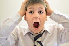 Muchacho adolescente que grita llevando a cabo sus manos detrás de la cabeza Foto de archivo