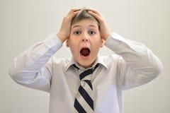 Muchacho adolescente que grita llevando a cabo sus manos detrás de la cabeza Imagenes de archivo