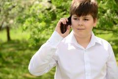 Muchacho adolescente que habla en el teléfono al aire libre Imagen de archivo libre de regalías