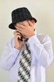 Muchacho adolescente que habla en el teléfono celular en el fondo ligero Imagen de archivo