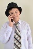 Muchacho adolescente que habla en el teléfono celular en el fondo ligero Imagen de archivo libre de regalías