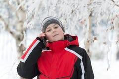 Muchacho adolescente que habla en el teléfono en parque del invierno Imagen de archivo libre de regalías