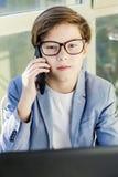 Muchacho adolescente que habla sobre el teléfono móvil y que usa el ordenador portátil Imágenes de archivo libres de regalías