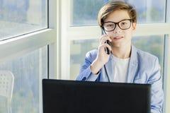 Muchacho adolescente que habla sobre el teléfono móvil y que usa el ordenador portátil Fotos de archivo