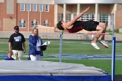 Muchacho adolescente que hace el salto de altura en la reunión de pista Imagen de archivo
