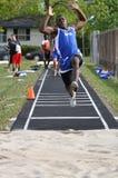 Muchacho adolescente que hace salto de longitud en la reunión del atletismo Fotos de archivo libres de regalías