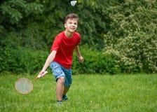 Muchacho adolescente que juega a bádminton en parque Imagen de archivo