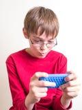 Muchacho adolescente que juega con el teléfono celular Imagenes de archivo