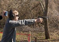 Muchacho adolescente que lleva a cabo el pistorl que fuma Imagenes de archivo