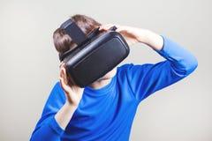 Muchacho adolescente que lleva los vidrios de la realidad virtual que miran películas o que juegan a los videojuegos Fotos de archivo libres de regalías