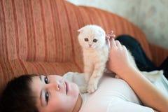 Muchacho adolescente que miente en el sofá con un gatito Fotografía de archivo libre de regalías