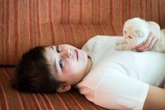 Muchacho adolescente que miente en el sofá con un gatito Foto de archivo