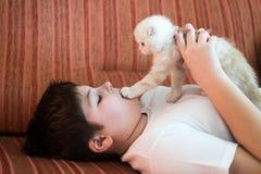 Muchacho adolescente que miente en el sofá con un gatito Imagenes de archivo