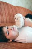 Muchacho adolescente que miente en el sofá con un gatito Fotos de archivo