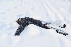 Muchacho adolescente que miente en la nieve Foto de archivo