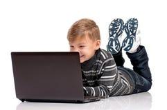 Muchacho adolescente que miente en piso con el ordenador portátil Imagenes de archivo