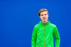 Muchacho adolescente que mira en cámara sobre el fondo del contraste al aire libre Foto de archivo