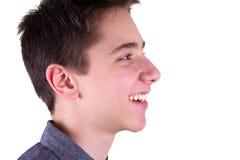 Muchacho adolescente que mira a su lado, sonriendo Aislado en el fondo blanco Fotografía de archivo