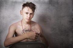 Muchacho adolescente que parece agresivo y que se sienta en una silla Imágenes de archivo libres de regalías
