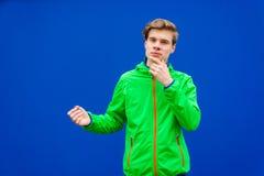 Muchacho adolescente que piensa sobre fondo del azul del contraste Foto de archivo libre de regalías