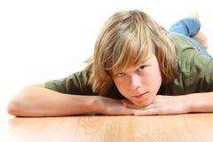 Muchacho adolescente que pone su cabeza en sus manos Imagen de archivo libre de regalías