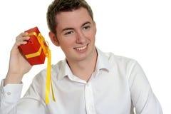 Muchacho adolescente que sacude el regalo de Navidad Imagen de archivo