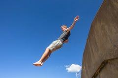 Muchacho adolescente que salta el cielo azul Imagen de archivo