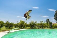 Muchacho adolescente que salta en bomba en una piscina al aire libre Fotografía de archivo