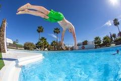 Muchacho adolescente que salta en la piscina azul Fotografía de archivo