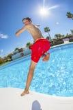 Muchacho adolescente que salta en la piscina azul Fotografía de archivo libre de regalías