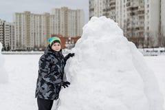 Muchacho adolescente que se coloca en el fuerte de expediente de la nieve Fotos de archivo libres de regalías