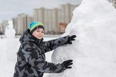 Muchacho adolescente que se coloca en el fuerte de expediente de la nieve Foto de archivo libre de regalías