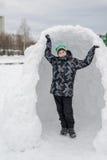 Muchacho adolescente que se coloca en fuerte de expediente de la nieve Foto de archivo