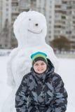 Muchacho adolescente que se coloca en un muñeco de nieve grande Imágenes de archivo libres de regalías