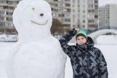 Muchacho adolescente que se coloca en un muñeco de nieve grande Fotos de archivo