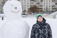 Muchacho adolescente que se coloca en un muñeco de nieve grande Imagen de archivo libre de regalías