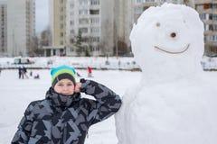 Muchacho adolescente que se coloca en un muñeco de nieve grande Foto de archivo libre de regalías