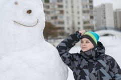 Muchacho adolescente que se coloca en un muñeco de nieve grande Fotografía de archivo