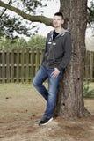 Muchacho adolescente que se inclina en árbol al aire libre Fotografía de archivo