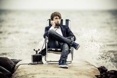 Muchacho adolescente que se relaja en la playa con el teléfono viejo Imagenes de archivo