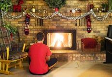 Muchacho adolescente que se sienta delante del fuego del rugido en la chimenea diciembre del ladrillo Foto de archivo libre de regalías