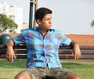 Muchacho adolescente que se sienta en banco de parque Fotos de archivo