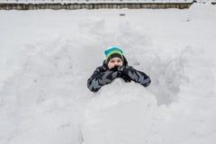 Muchacho adolescente que se sienta en fuerte hecho en casa de la nieve Fotografía de archivo libre de regalías