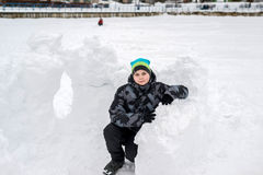Muchacho adolescente que se sienta en fuerte hecho en casa de la nieve Fotografía de archivo